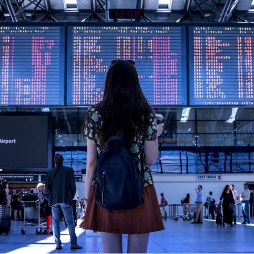 Girl standing in front of airport flight arrivals-departures board.