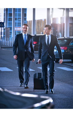 Airport shuttle driver carrying bag to car